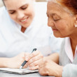 Senior woman solving a crossword , nurse helping - Stock Photo
