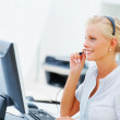 Royalty-Free Stock Photo: Cute young call centre employee working on a computer