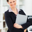 Pretty woman holding a business file while at work - Stock Photo