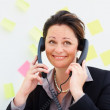 Business woman using two phones at a time - Stock Photo