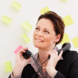 Business woman with two telephone receivers , lost in thought - Stock Photo