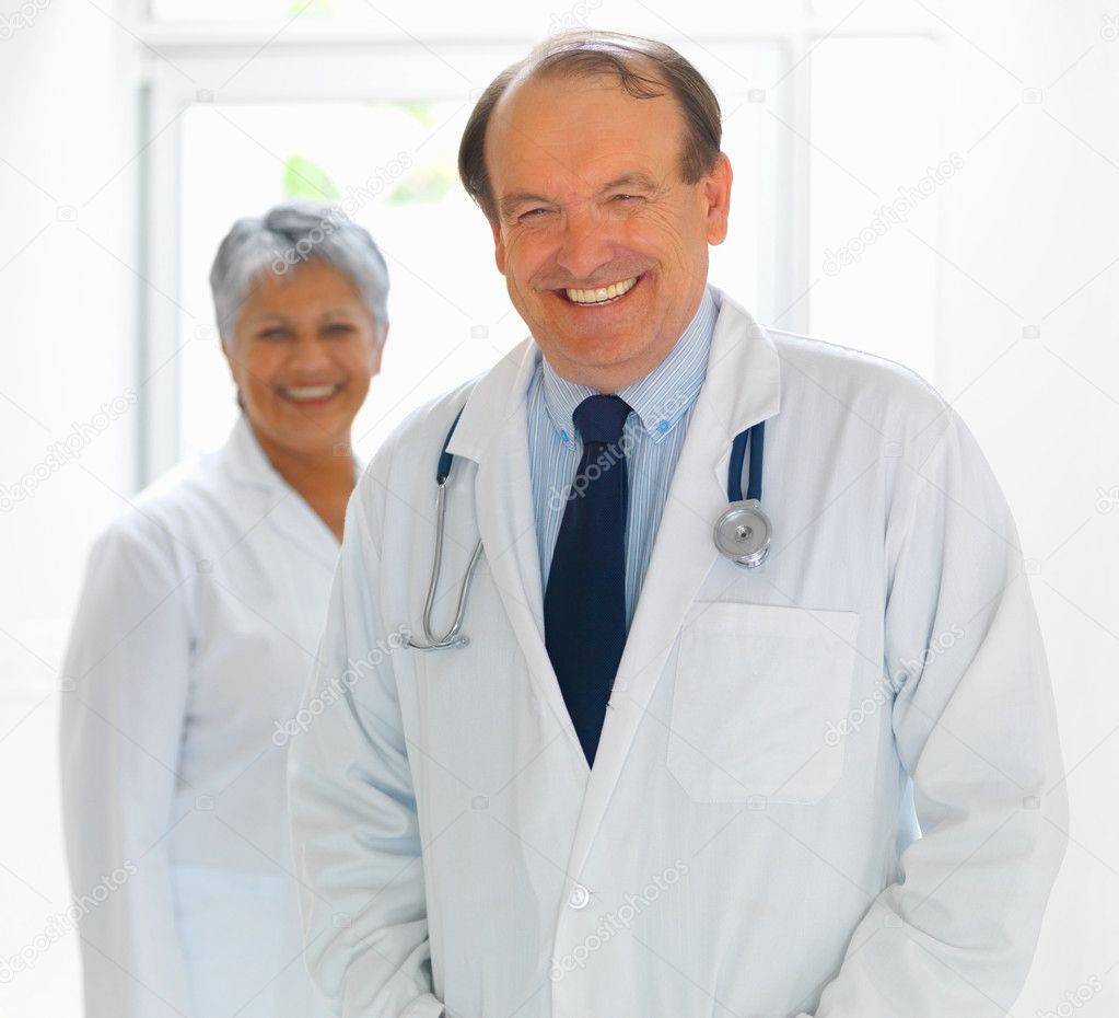 Happy successful doctor at work , female colleague at the background  Stock Photo #3340822