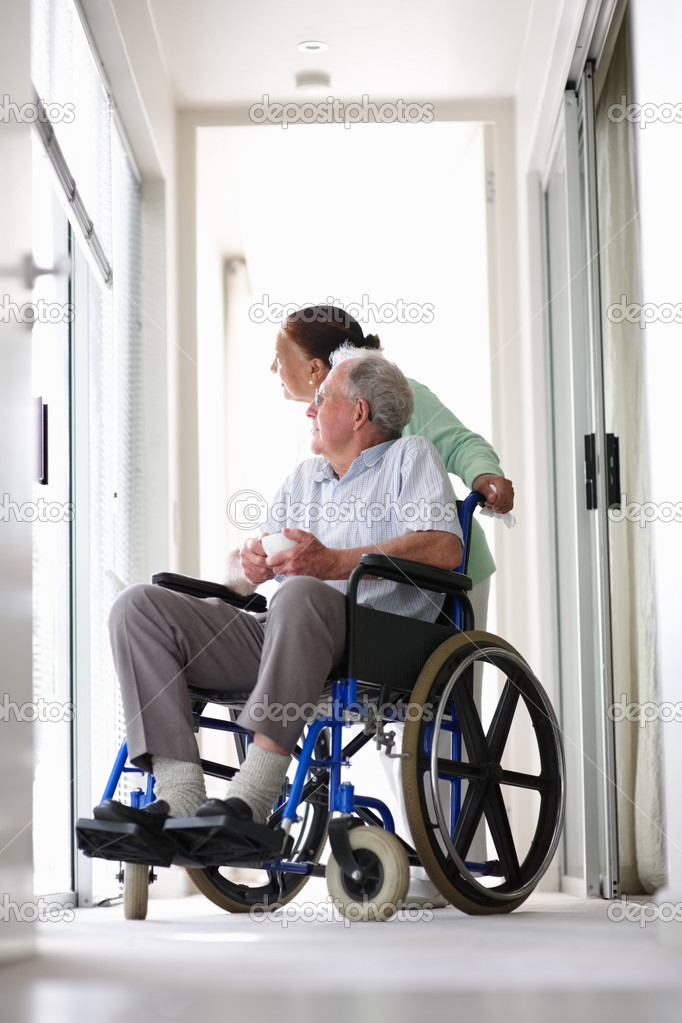 Retired couple at the hospital looking outside , senior man on the wheelchair — Stock Photo #3341787