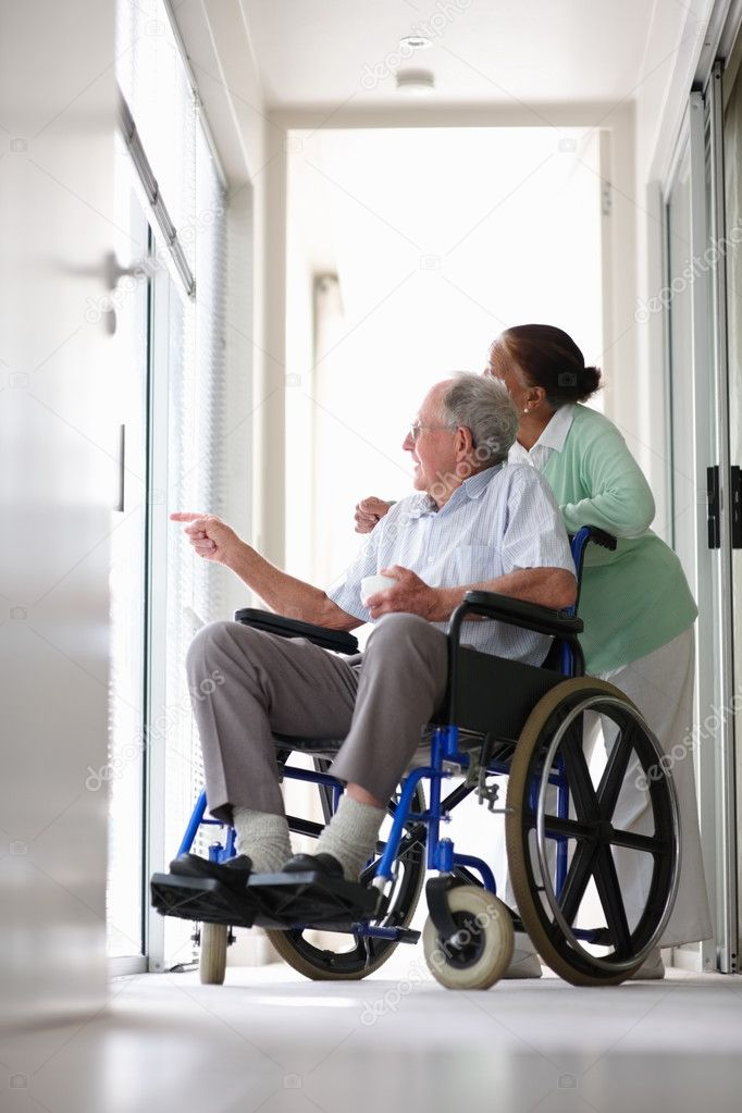 Retired couple at the hospital looking outside , elderly man on the wheelchair  Stock Photo #3341793