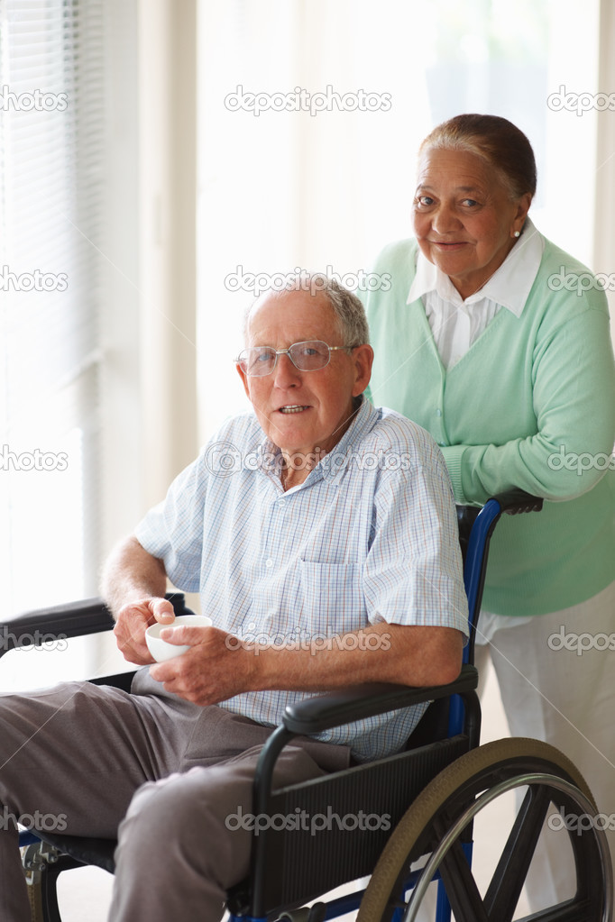 Portrait of a senior citizen couple at a hospital , man on the wheelchair  Stock Photo #3341795