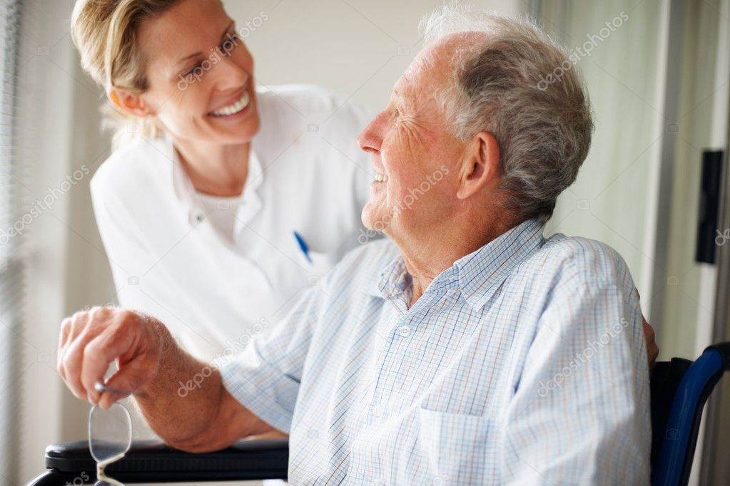 Happy retired man at the hospital speaking with a young nurse  Stock Photo #3341832
