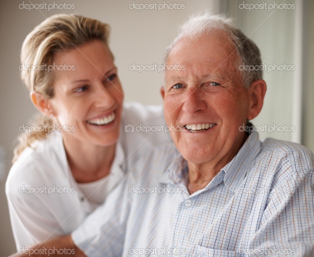 Closeup portrait of a happy senior man on a wheel chair with a nurse for assistance — Stock Photo #3341844
