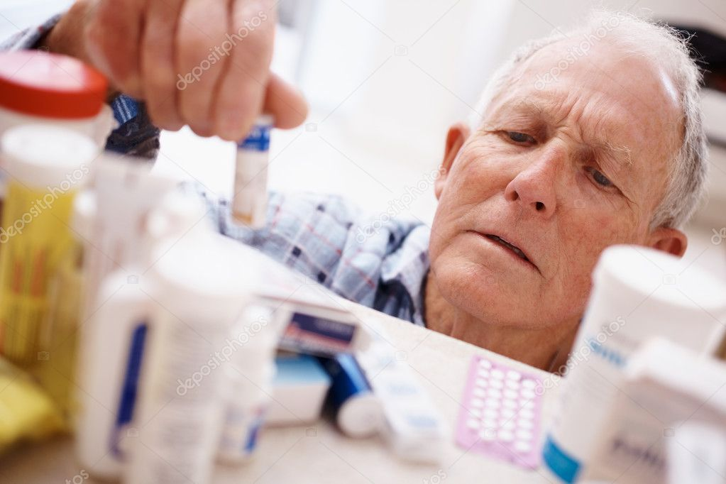 Elderly man picking a medicine bottle from a shelf — Stock Photo #3342023