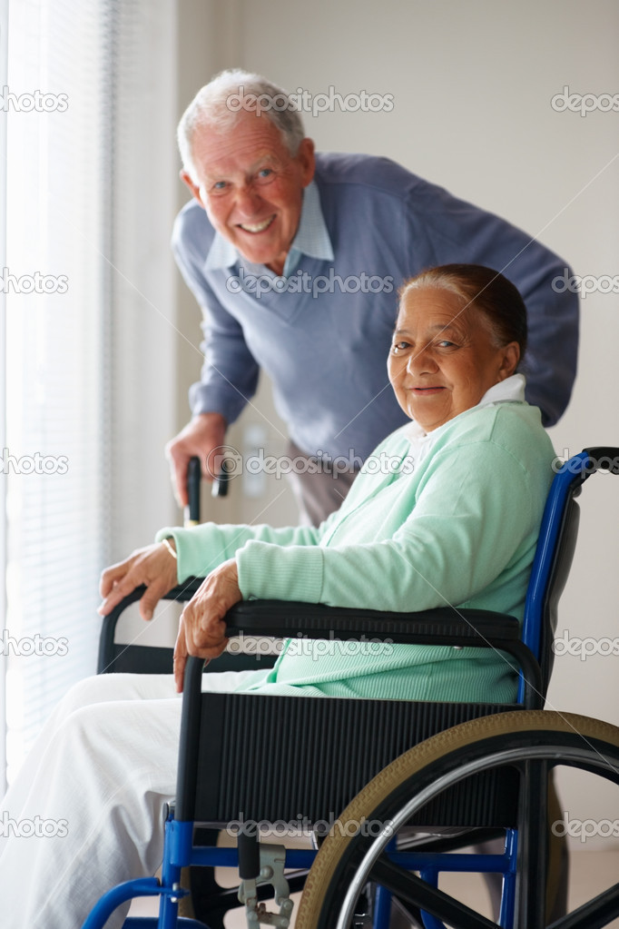 Happy senior woman on a wheel chair , husband at the back — Stock Photo #3342263