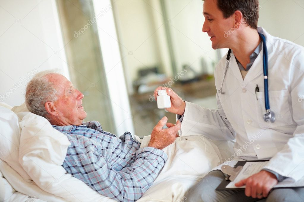 Young doctor giving a bottle of pills to a patient , old man having a word with the doctor — Stock Photo #3342500