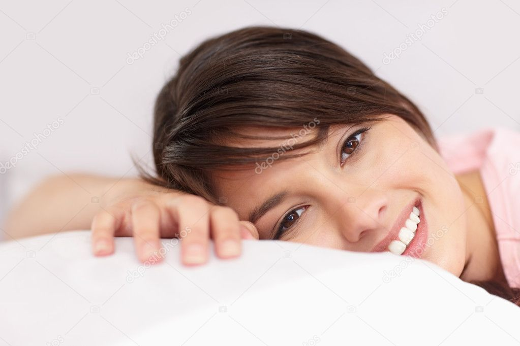 Cute young female relaxing on a pillow in bed  Foto de Stock   #3342800