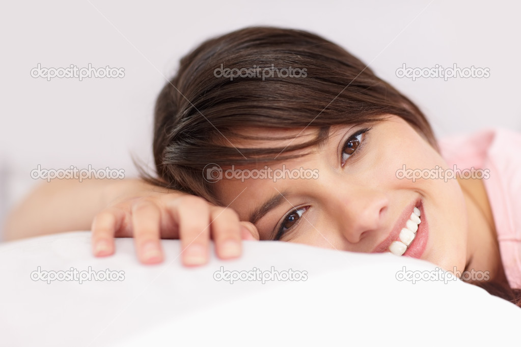 Cute young female relaxing on a pillow in bed — Foto de Stock   #3342800