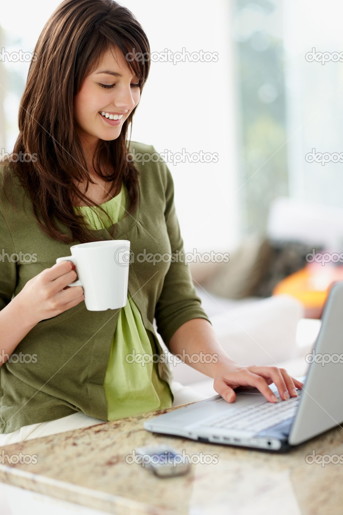 Happy young female having a cup of coffee using the laptop at home — Stock Photo #3342921