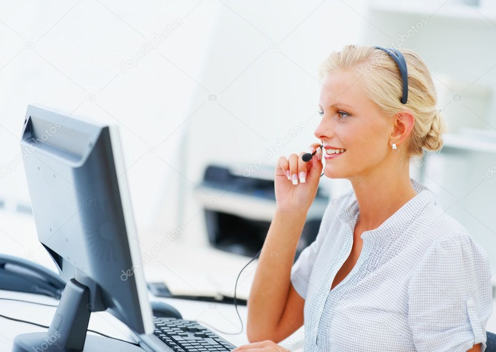 Young pretty call centre employee conversing over the headset , using the computer — Stock Photo #3343277