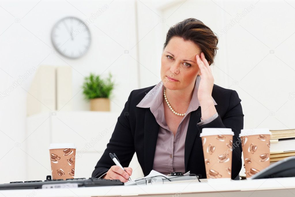Depressed middle aged business woman with hand on head at work  Stock Photo #3343424
