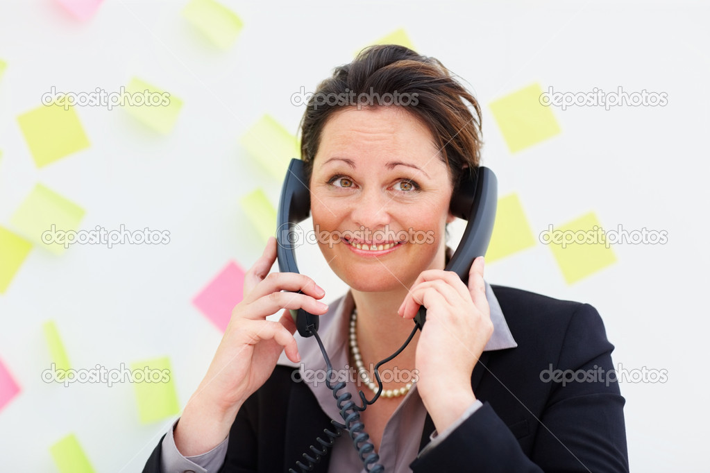 Pretty mature business woman speaking on two phones at the same time  Stock Photo #3343442