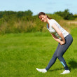 Young woman doing exercise outdoors - Stock Photo