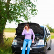 Car breakdown - Young lady calling for assistance - Stock Photo