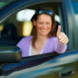 Woman showing thumbs up sign in car - Stock Photo