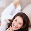 Happy thoughtful mature woman lying on couch - Foto Stock
