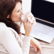 Pretty woman having coffee in front of laptop - Stockfoto