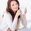 Cute woman holding coffee cup while using laptop - Stockfoto