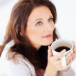Happy woman having coffee , lost in thought - 