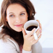 Happy woman having coffee looking away in thought - Foto Stock