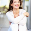 A cheerful woman looking away in thought - Stockfoto