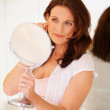Happy mature female looking into mirror - Stock Photo