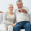 Royalty-Free Stock Photo: Charming senior couple sitting on a sofapointing remote control