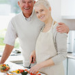 Royalty-Free Stock Photo: Smiling senior couple preparing food in the kitchen