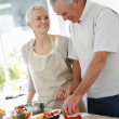 Elderly couple cooking food together - Stock Photo