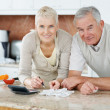 Royalty-Free Stock Photo: Elderly couple calculating their bills at the kitchen
