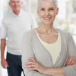 Royalty-Free Stock Photo: Older woman standing with her husband in the background