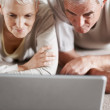 Senior couple looking at the screen of a laptop computer - Stock Photo