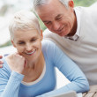 Royalty-Free Stock Photo: Smiling elderly man and woman using a laptop
