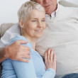 Royalty-Free Stock Photo: Senior man hugging his wife while on a couch