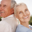 Closeup of a smiling elderly couple sitting back to back - Stock Photo