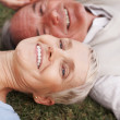 Royalty-Free Stock Photo: Elderly couple holding hands while lying on grass