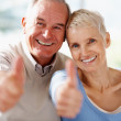 Royalty-Free Stock Photo: Smiling senior couple showing a success sign