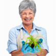 Happy older female gardener holding a plant in her hand - Foto Stock