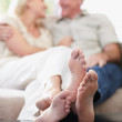 Royalty-Free Stock Photo: Couple sitting on sofa with feet propped on table, focus on feet