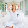 Royalty-Free Stock Photo: Yogatic - Pretty woman sitting on bed and meditating