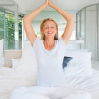 Female sitting on bed and meditating for a better life - Stockfoto