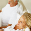 Thoughtful woman lying in bed besides husband - Foto Stock