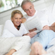 Couple in bed reading the newspaper together - Stock Photo