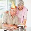 Senior man blowing out birthday candles on his birthday - Stock Photo