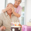 Birthday surprise - Senior woman covering husband's eyes - Stock Photo