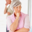 Senior lady and her husband looking away after an argument - Stock Photo